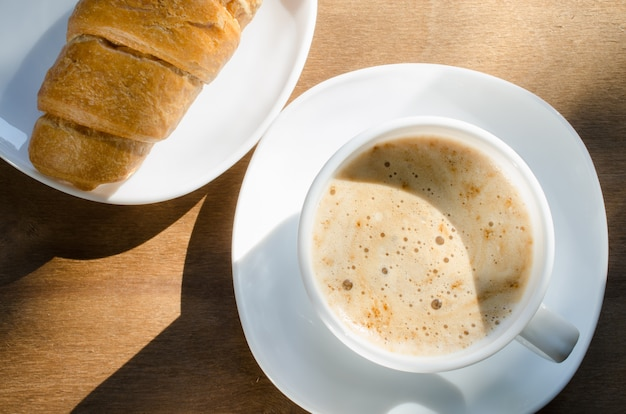 Cappuccino or coffee latte and croissant.