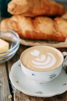 一斤のパンと木製のテーブルの上のカプチーノコーヒーバターを塗ったパンと朝食