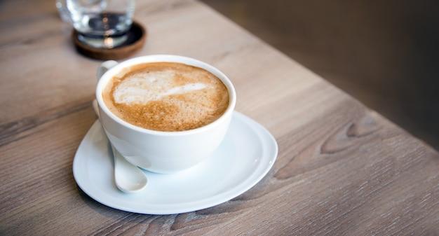 테이블 아침에 카푸치노 커피가 배너 크기의 세라믹 컵에 제공됩니다.