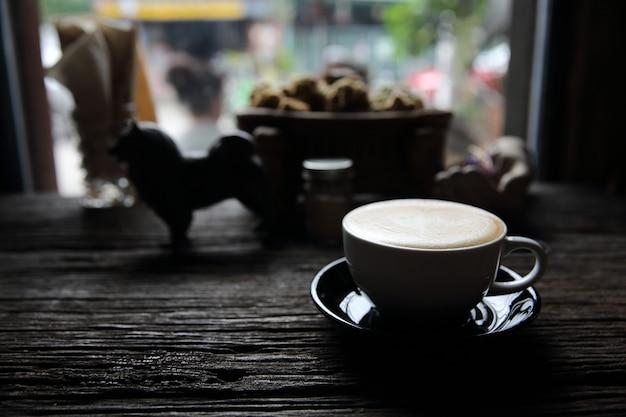 木の背景にカプチーノコーヒー