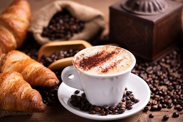 Кофе капучино над темными жареными кофейными зернами крупным планом