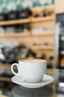 Cappuccino coffee with art latte on reflective glass in caf�