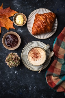 Cappuccino coffee with croissant on the table, autumn breakfast concept, top view