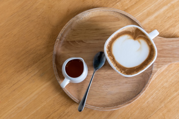Cappuccino cup coffee with sugar and spoon on wooden plate and wooden table, top view