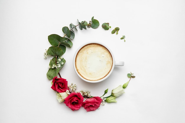Cappuccino and flowers composition. white coffee cup with creamy foam, fresh flowers circle at white, top view. hot drinks, seasonal offer concept.