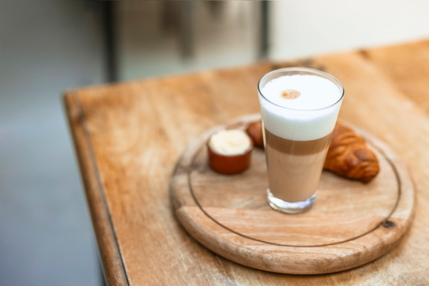 Cappuccino in glass with croissant on wooden circular tray