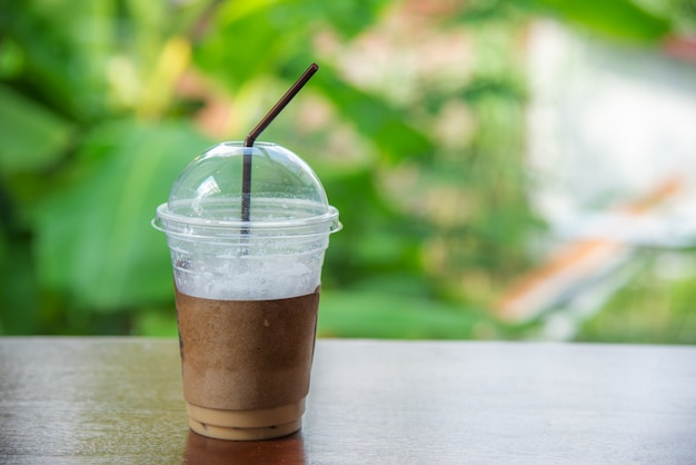 Cappuccino ice coffee in a glass on blurred bokeh