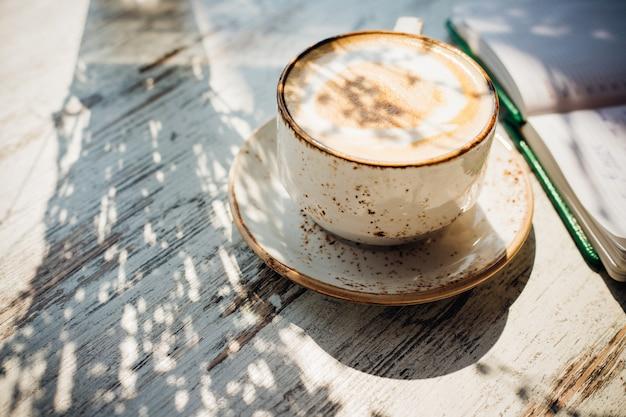 美しいセラミックカップに入ったカプチーノがカフェのテーブルの上にあります。おいしい香りのよい朝食。