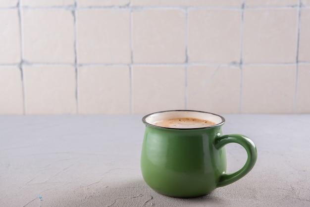 キッチンテーブルの上のカップのカプチーノ