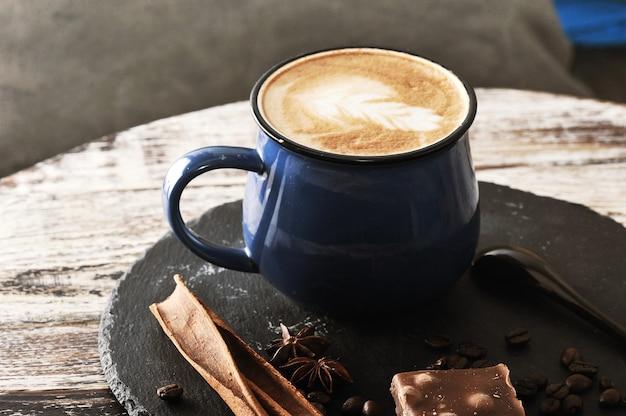 ミルクフォームとシナモンとチョコレートが入ったマグカップのカプチーノ