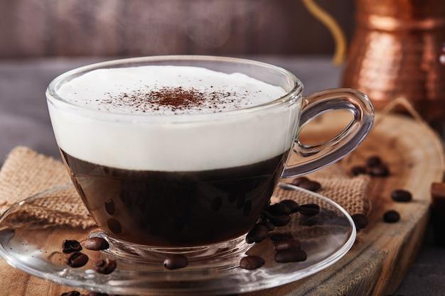 카푸치노는 에스프레소 기반 커피 음료이며 투명 유리 컵에 커피로 만든 찐 우유 거품입니다. 증기와 뜨거운 커피