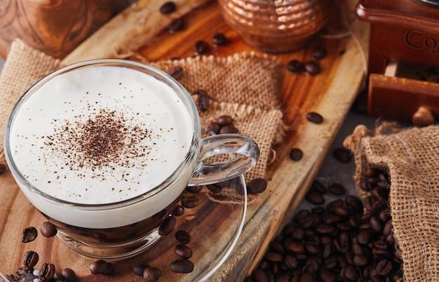카푸치노는 에스프레소 기반 커피 음료이며 투명 유리 컵에 커피로 만든 찐 우유 거품입니다.