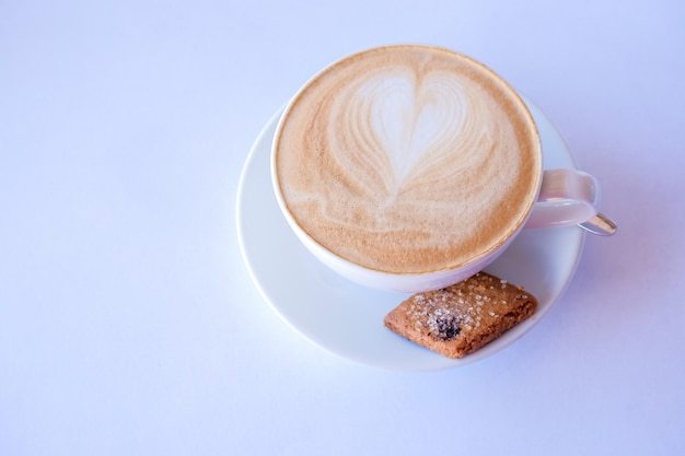 Cappuccino or latte coffee in cup with frothed milk and cookies.cup of coffee with almond biscotti. latte with heart design.