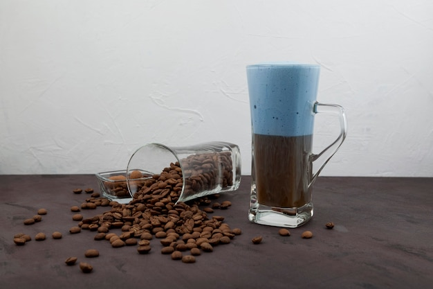 Cappuccino or latte coffee with blue milk foam in tall glass.