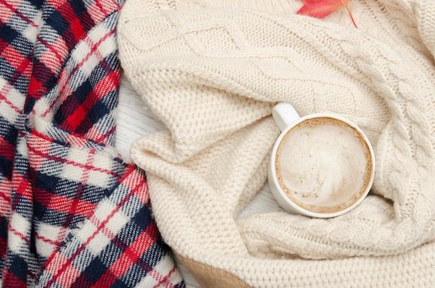 カプチーノ、ミルクニットのセーター、チェック柄のチェック柄、紅葉。ファッショナブルなコンセプト