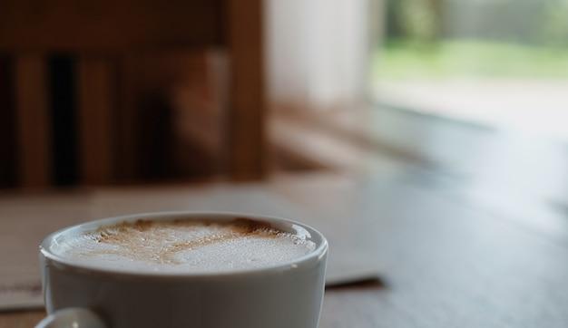 木製のテーブルにカプチーノまたはコーヒーラテ。クローズアップ、セレクティブフォーカス、窓からの日光。コーヒーブレイクのアイデア、コーヒーブレイク