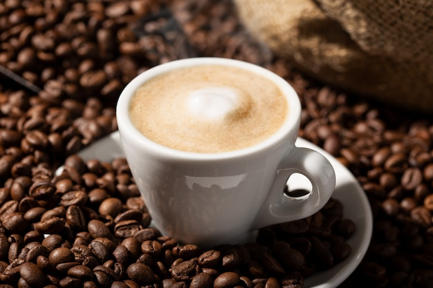 カプチーノまたはコーヒーとミルクカップとロースト豆。コーヒーの背景