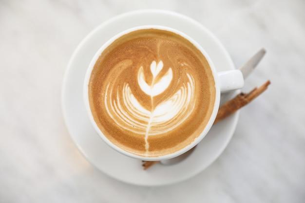 커피 숍의 흰색 테이블에 우유로 만든 카푸치노 또는 라떼 아트 커피