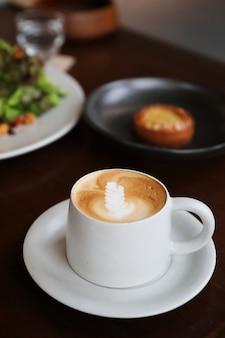 Капучино или кофе латте-арт из молока на деревянном столе в кафе