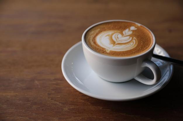 커피 숍의 나무 테이블에 우유로 만든 카푸치노 또는 라떼 아트 커피