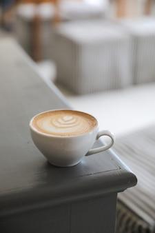コーヒーショップの木製テーブルに牛乳から作られたカプチーノまたはラテアートコーヒー