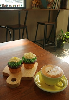 Cappuccino and two cupcakes topped with flower shaped whipped cream served in a cozy room