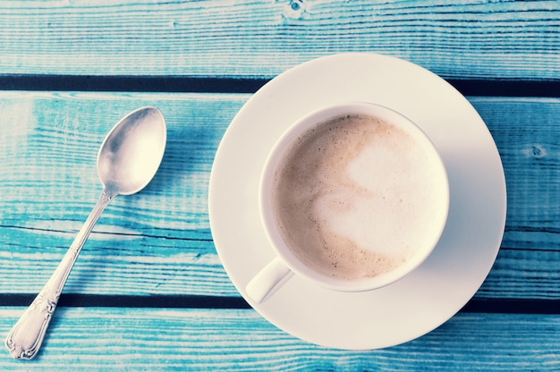 Cappuccino in a white mug on blue table
