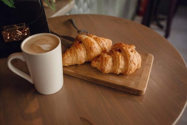 Капучино с красивым латте-артом и круассаном на деревянном фоне на столе. идеальный завтрак по утрам. деревенский стиль.