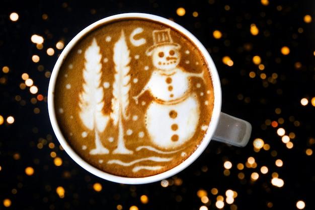 木製の背景にいくつかのぼやけたライトとクリスマス雪だるまアートとカプチーノ