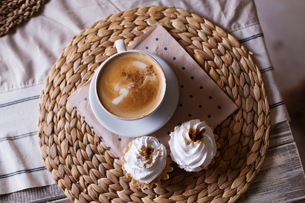Cappuccino with cinnamon, cake with airy white cream on a straw napkin, top view