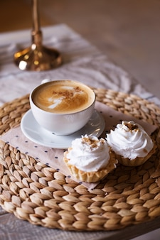 Cappuccino with cinnamon, cake with airy white cream on a straw napkin