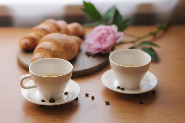 クロワッサンとカプチーノ。自宅でコーヒーの木製テーブル2杯。空のクロワッサン。テーブルの上のピンクの牡丹の花。