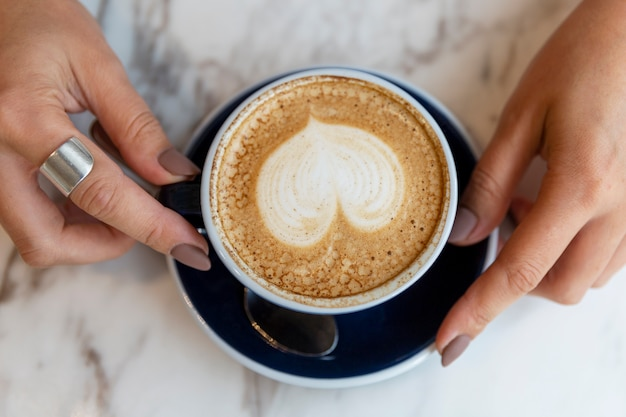 Cappuccino with heart-shaped foam in a blue cup on a marble table surface in female hands.