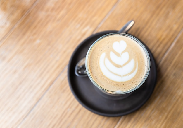 Cappuccino with latte art in glass cup on wooden table in cafe or coffeehouse