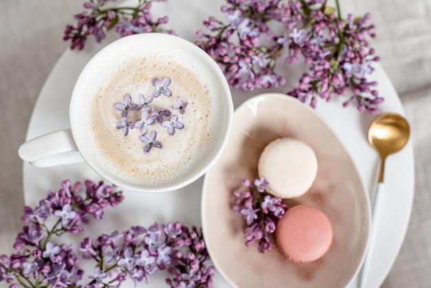 Капучино с макарунами на льняной скатерти, цветы фиалки, утренняя концепция