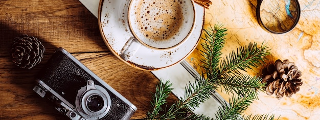 Cappuccino on a wooden table, tourist map and camera. long banner