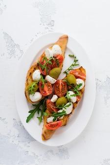白いプレートの古い光の表面にチェリートマト、モッツァレラチーズ、オリーブ、バジルを添えたカプレーゼブルスケッタトースト。上面図。