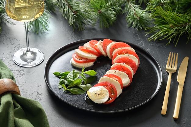 クリスマスのカプレーゼキャンディケインホリデー前菜は、黒いテーブルでお召し上がりいただけます。クリスマスパーティー。閉じる。