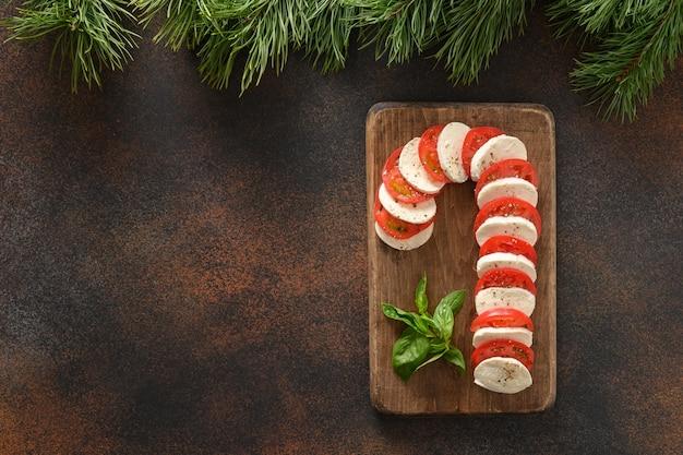 カプレーゼキャンディケインサラダは、お祝いのクリスマスパーティーの休日の前菜です。上からの眺め。スペースをコピーします。