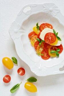 Капрезе свежие красочные помидоры и листья базилика в керамической миске на белом фоне