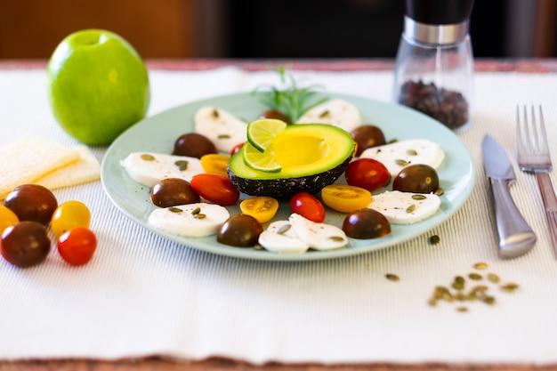 カプレーゼサラダ。チーズモッツァレラチーズとチェリートマト、コショウ、カボチャの種が入った料理。健康的な菜食主義の食事を補完するための半分のアボカドと青リンゴ