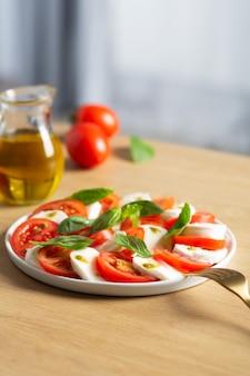 카프레제 샐러드. 신선한 토마토, 모짜렐라 치즈, 바질을 곁들인 이탈리아의 유명한 샐러드. 주방과 테이블