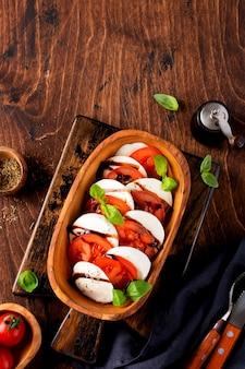 오래 된 소박한 배경에 올리브 나무 그릇에 익은 토마토, 신선한 정원 바질, 모짜렐라 치즈와 함께 카프레제 샐러드 이탈리아 음식. 평면도 평면도