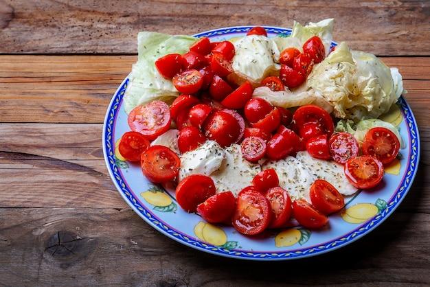 Caprese salad.mediterranean. mozzarella cherry tomatoes basil and olive oil on old oak table. italian cuisine