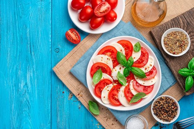 Салат капрезе из нарезанных свежих помидоров, сыра моцарелла, базилика и оливкового масла на синем деревянном столе. традиционная итальянская кухня