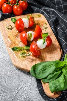 串、トマト、ペスト、モッツァレラチーズのカプレーゼサラダ。カナッペスナック。灰色の背景。上面図
