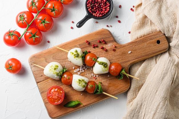 Caprese salad on sticks cherry tomatoes, mozzarella cheese, basil, pesto sauce on wood board