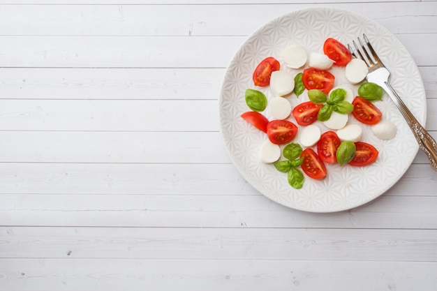 Caprese salad of tomatoes, mozzarella cheese and basil on a white plate. italian cuisine. copy space