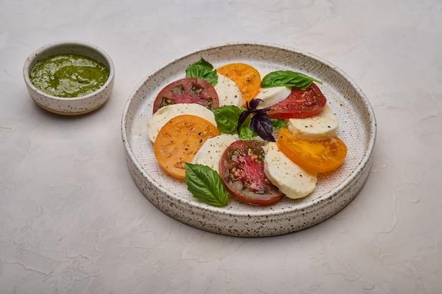 赤と黄色のトマトのペストバジルとモッツァレラチーズの白いプレートのカプレーゼサラダをクローズアップ