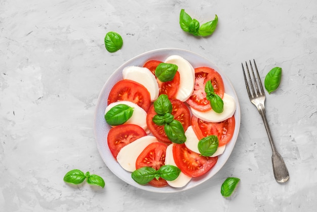 Caprese salad with ripe tomatoes and mozzarella cheese, fresh basil leaves and fork. italian food